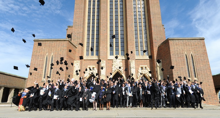 University of Surrey graduates throwing their mortar-boards in the air outside Guildford Cathedral