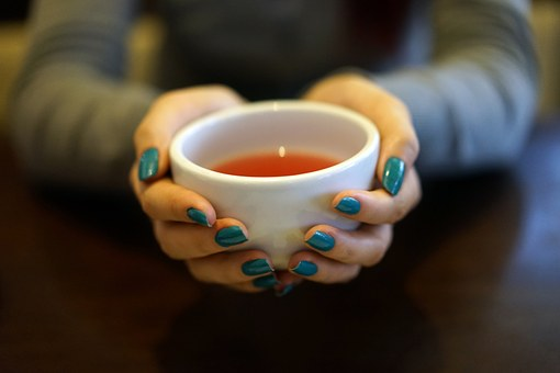 Hands with blue nail varnish cupping a soothing cup of tea
