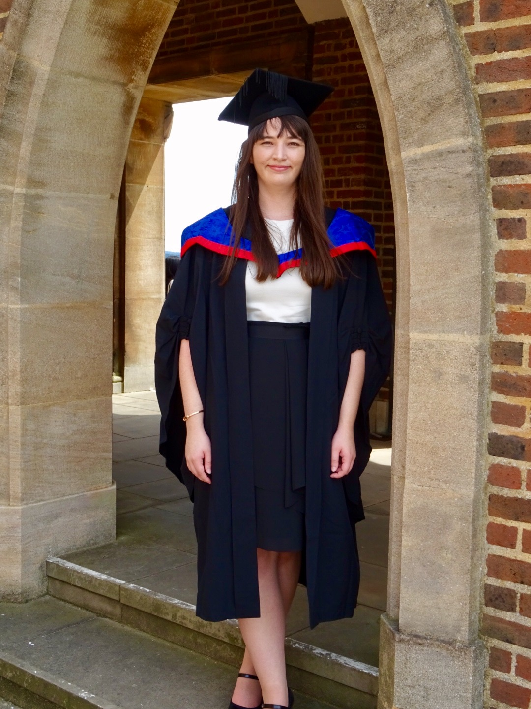 Rosie the author of this blog. stands under an archway at the University of Surrey in her graduation gown.