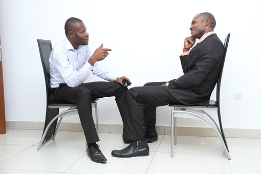 image of 2 men seated opposite each other, one talking animatedly and one listening with interest
