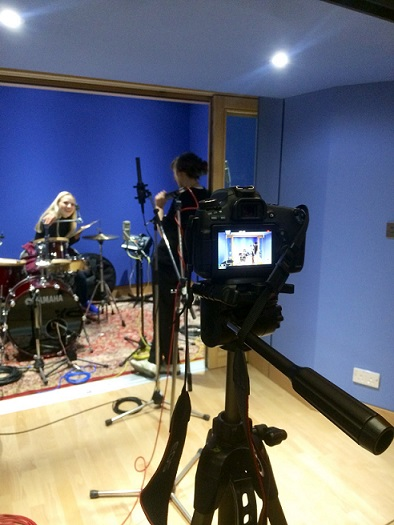 A view of a recording session at Abbey Road studios featuring a female singer and drummer