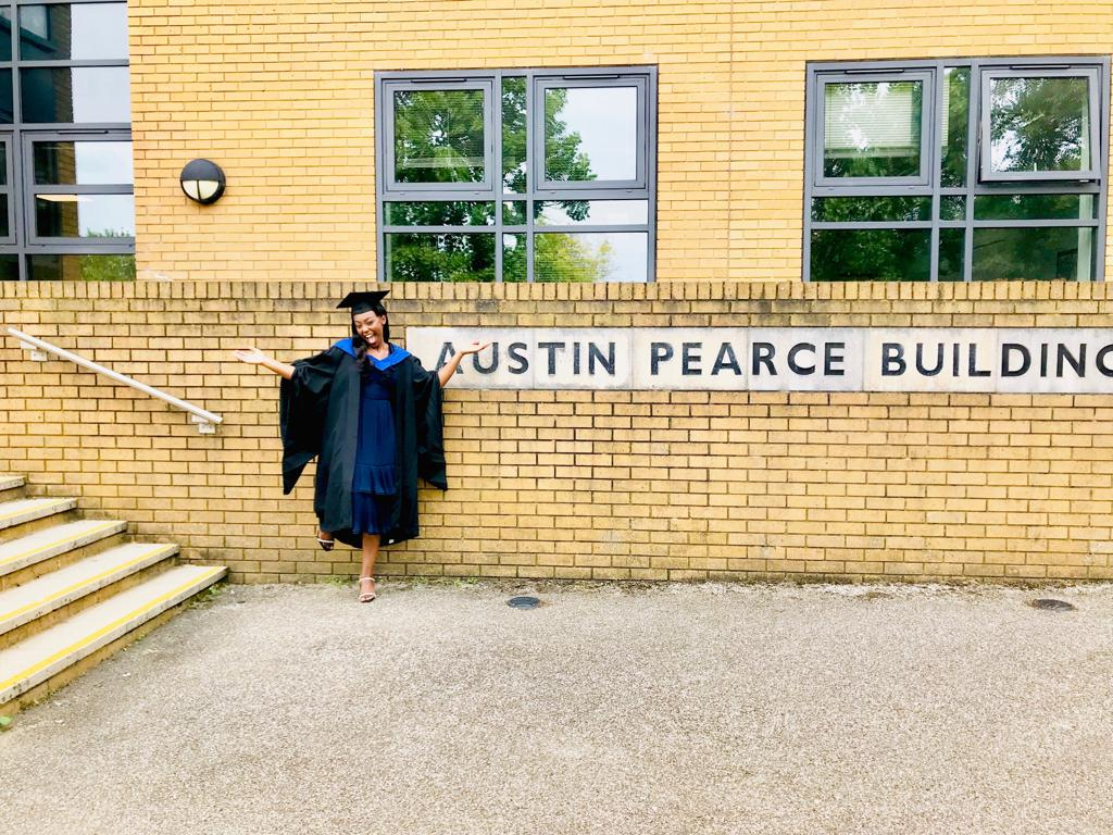 Toni outside the Austin Pearce building in graduation robes