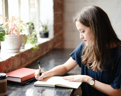 Student or graduate writing down her summer plans