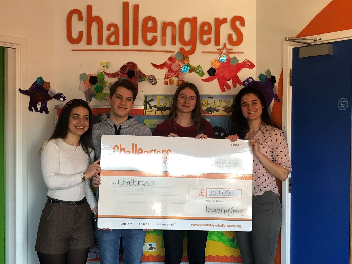 4 University of Surrey students holding a cheque for £360 for Challengers
