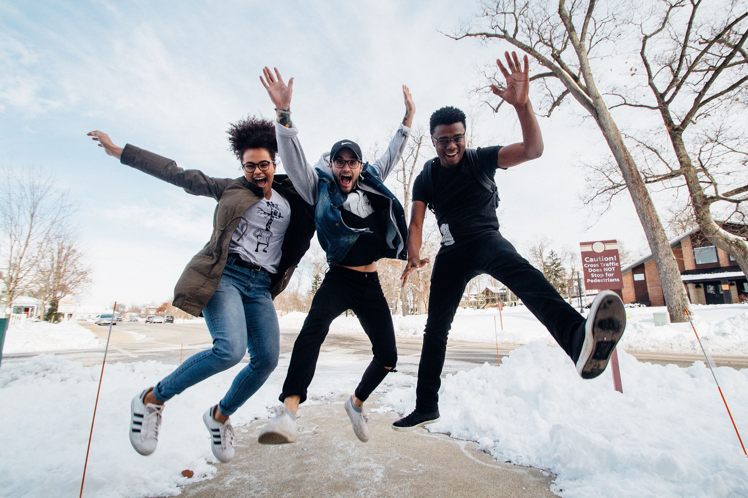 3 students jumping in the air with snow on the ground beneath them