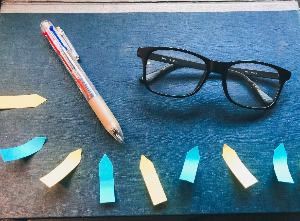 Some post it notes, a pen and a pair of glasses