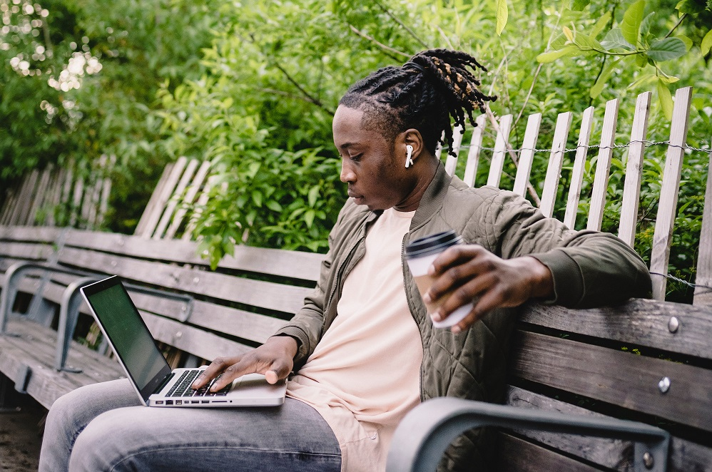 Placement student with dreadlocks sitting on a bench with a laptop and a coffee