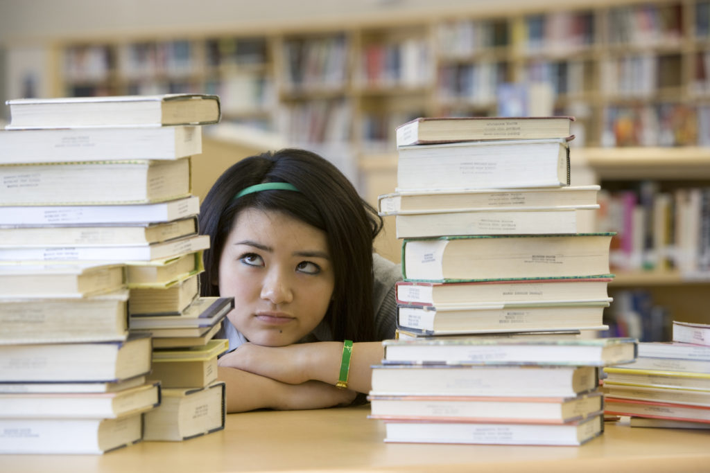 Student in library surrounded by books