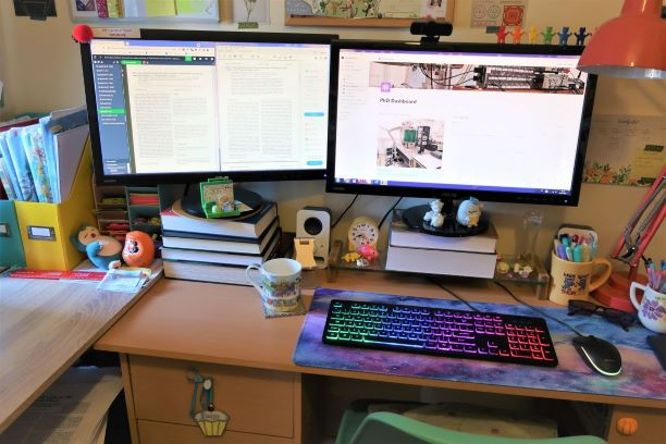 A desk with two monitors stnading on books. A colourful keyboard is sitting in front of the right hand monitor. There is a mug of tea next to the keyboard.