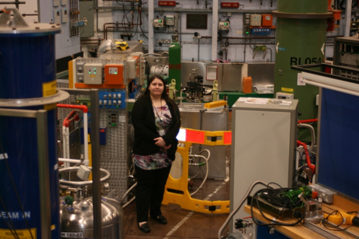 Image of the student standing in front of a large scientific instrument