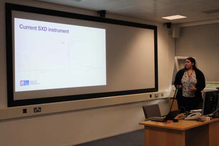 Image of the student delivering a presentation on her project. She is gesturing to graphs on a big screen