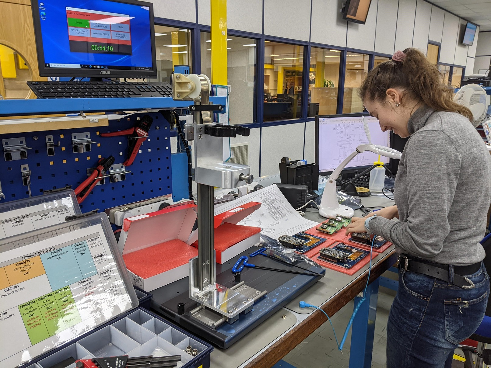 Lisa working on a circuit board during her engineering placement at Stanhope-Seta. She is surrounded by equipment and computers