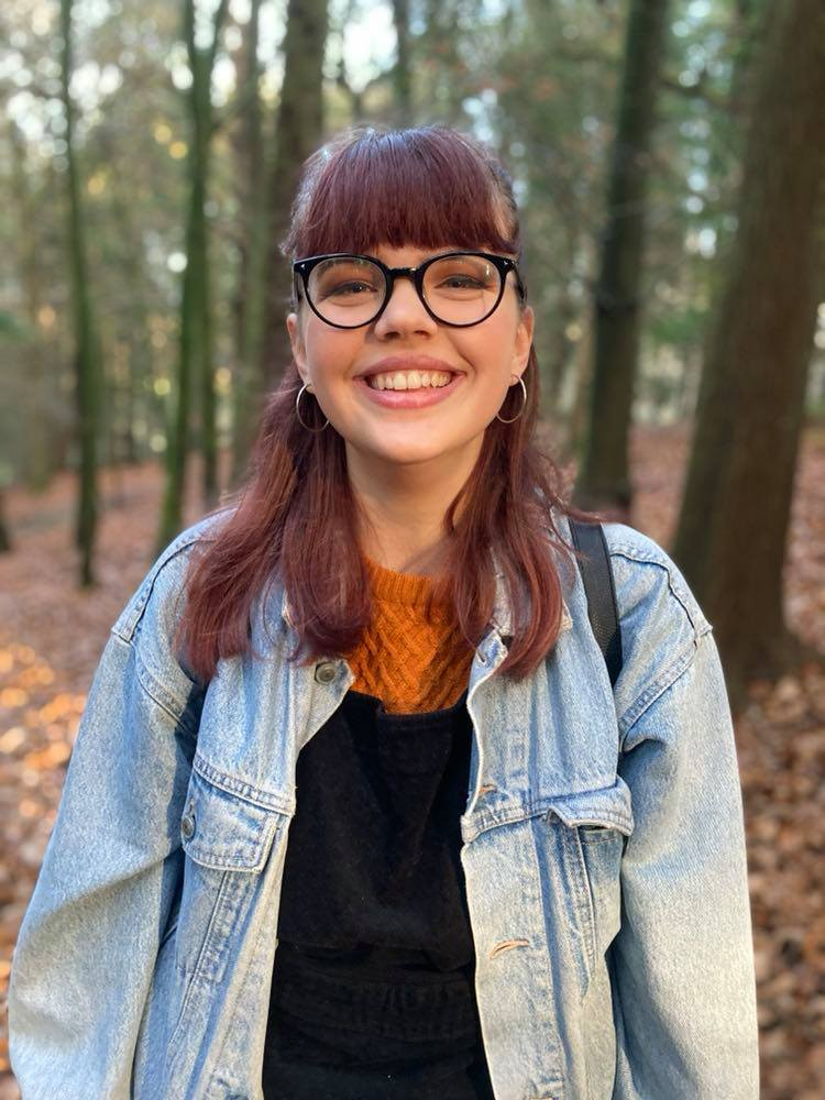 A photo of a young woman smiling, the background is in the woods