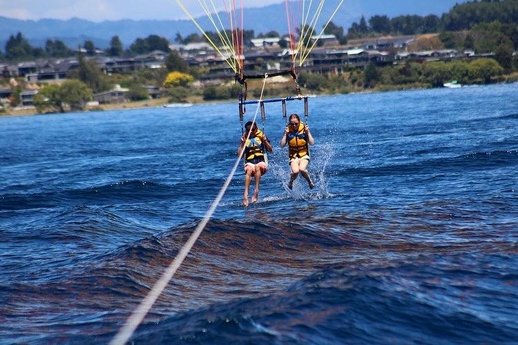 Two people parasailing, splashing their feet in the water.