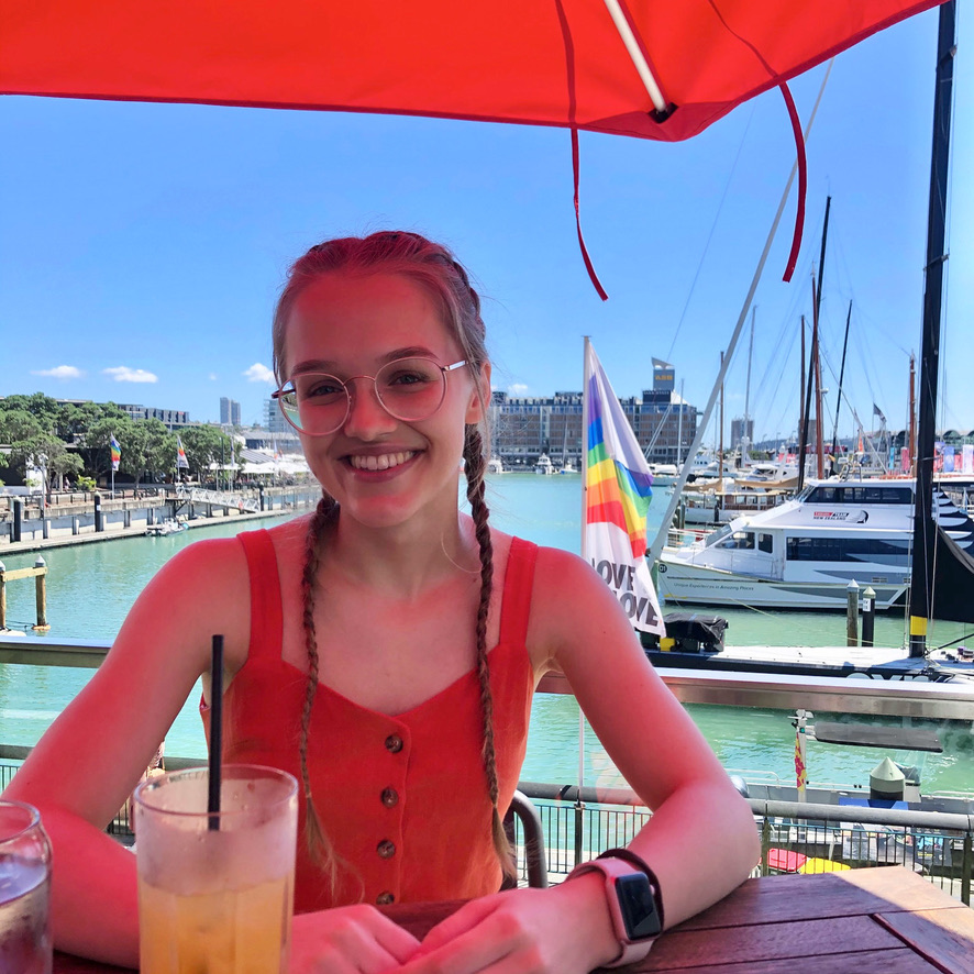 A girl smiling at the camera, with a harbour in the background.