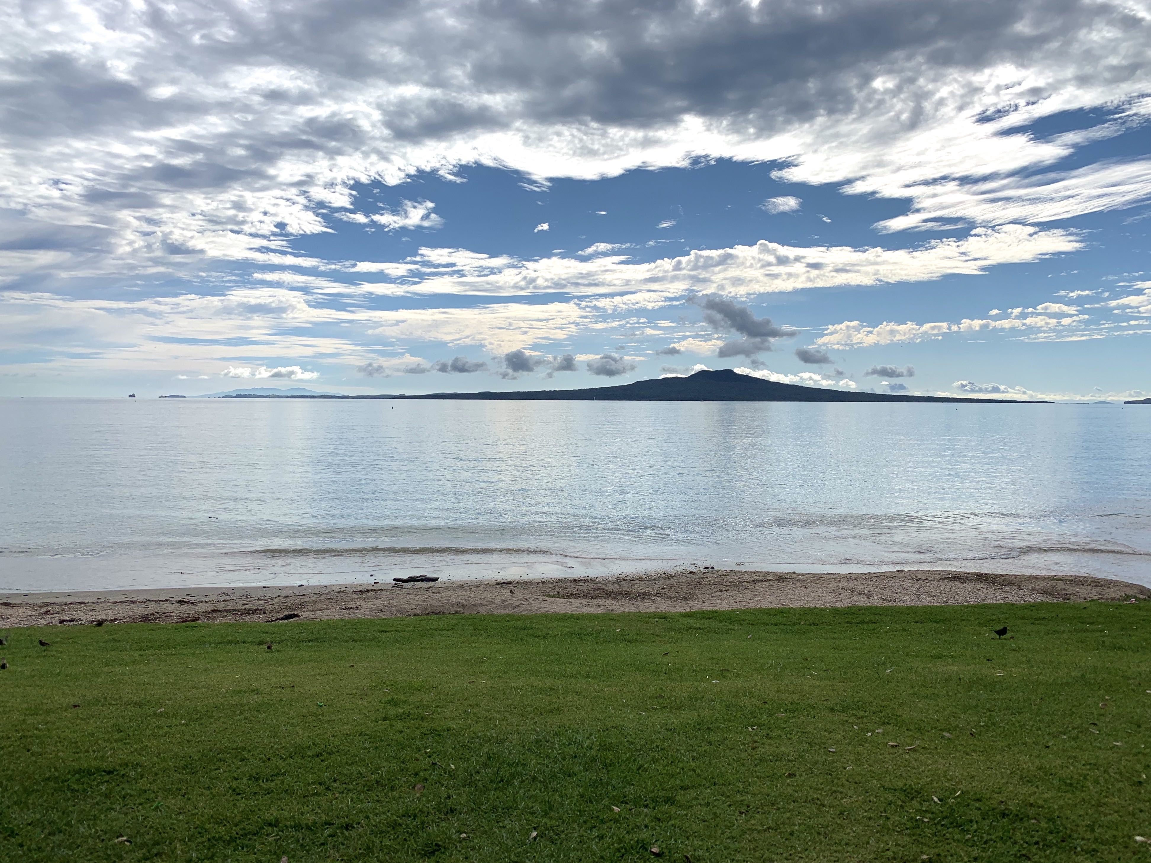 A beach with the tide in. Grass in the foreground and a volcano in the background.