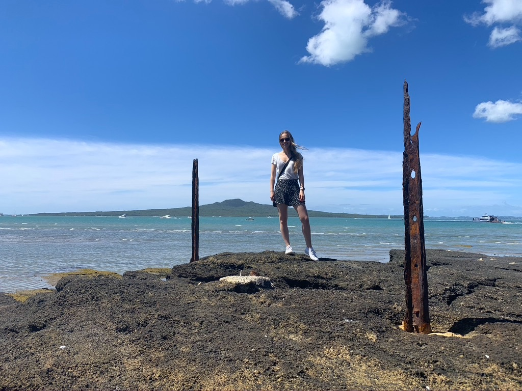 A girl standing on a rock, posing in front of the ocean and a volcano in the background.