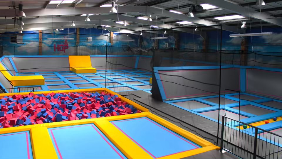 A photograph of Airhop Guildford empty. It shows a series of trampolines and a pit filled with foam cubes