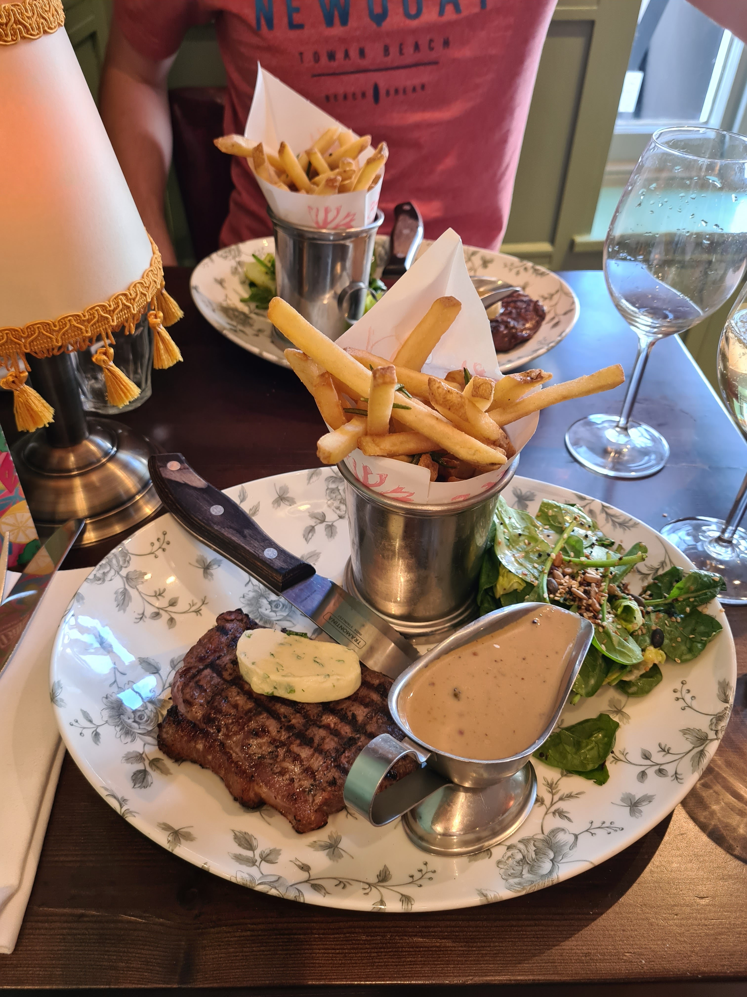 A photograph of two steaks with chips and a salad. Taken at Bill's in Guildford